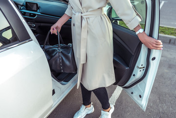 woman opens door of business class taxi car, bag in her hand after shopping, fashionable modern fashion girl, car sharing rental. In autumn summer, parking shopping center.