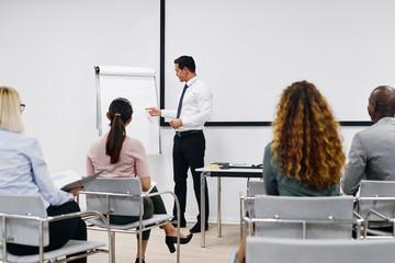 Manager explaining business concepts during a presentation to em