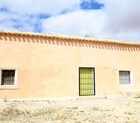 Façade de maison rose avec fenêtres à barreaux.