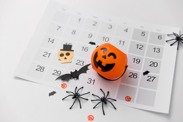 halloween, decorations and holidays concept - jack o lantern, spiders, bats and calendar on white...