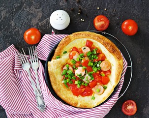 Dutch baby pancake filled tomatoes, sausages and cheese in a serving cast-iron frying pan on a dark concrete background. Danish cuisine. Hearty breakfast recipes.