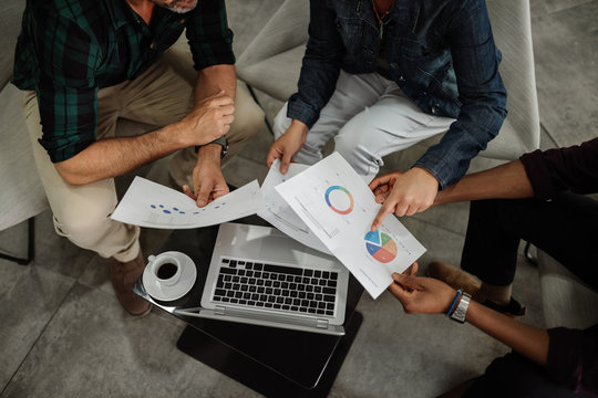 Aerial view of diverse business team analyzing financial data