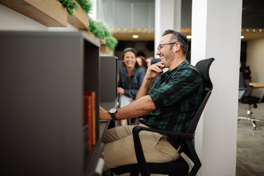 Handsome stylish entrepreneur interacting and working in modern coworking office workspace