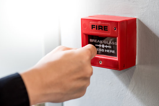 Male hand punching red fire alarm switch on concrete wall in public building. Industrial fire warning system equipment for emergency.