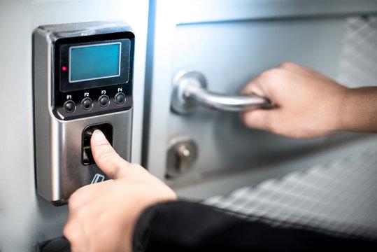 Scanning fingerprint to open security door in private building. Unlock concept