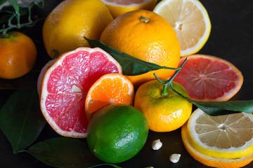 fresh citrus fruits orange, mandarin, lime, grapefruit, lemon and green leaves on a black background close-up