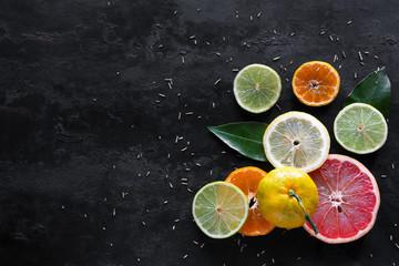 slices of fresh citrus fruits (orange, mandarin, lemon, lime, grapefruit) on a black background with place for text