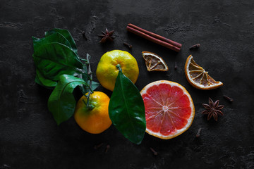 Fresh citruses and spices on a black background. Vitamin C immunity strengthening concept.