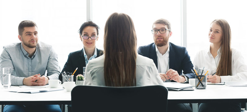 Woman at job interview talking with members of management