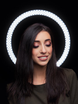 Beautiful young caucasian woman trendy look portrait with ring light halo black background for makeup artist portfolio in film effect colors