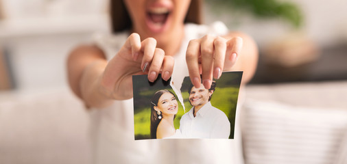 Unrecognizable Girl Tearing Apart Photo Of Happy Couple Indoor, Cropped