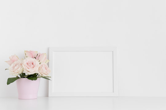 White frame mockup with pink roses in a pot on a white table.Landscape orientation.