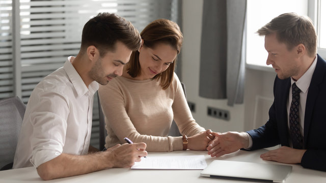 Young couple making deal with manager, signing contract