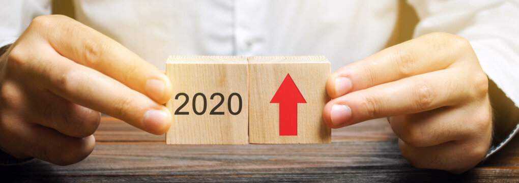Businessman holds wooden blocks with the inscription 2020 and an up arrow. The forecast concept for 2020. Business forecasting. Growth and development of business and economy. Investments