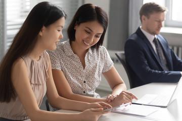 Fototapeta Happy Asian businesswomen colleagues using phone, chatting during break obraz