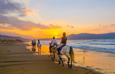 A group of girls on horseback riding on a sandy beach on the background of the sunset sky
