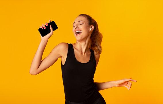 Girl In Wireless Earphones Holding Phone Dancing Listening Music, Studio