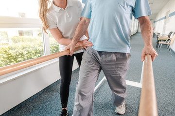 Senior Patient and physical therapist in rehabilitation walking exercises