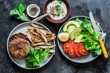 Grilled turkey, wholegrain bun, avocado, tomatoes, green salad and greek yogurt mustard sauce - ingredients for cooking hamburger on a dark background, top view