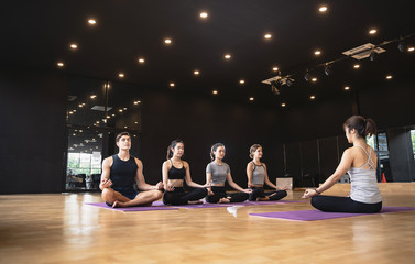 Group of mix race people practicing yoga meditating together for Healthy lifestyle in fitness club