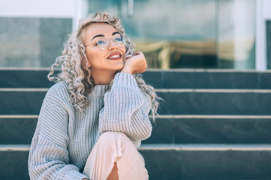 Plus size model with blond curly hair in knitted sweater outdoor