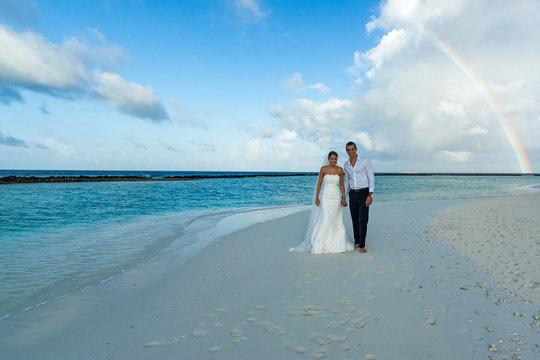 Hochzeitspaar läuft am Strand auf den Malediven unter einem Regenbogen