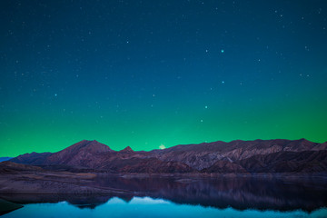 Beautiful lake and mountains in the starry night with green light over the mountains. Night landscape.