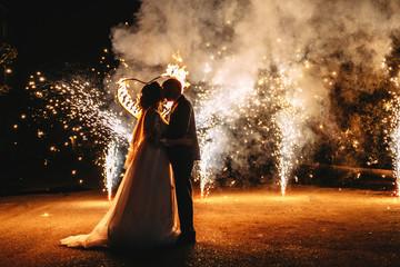 Wedding fireworks. Wedding couple silhouettes. Fire show.