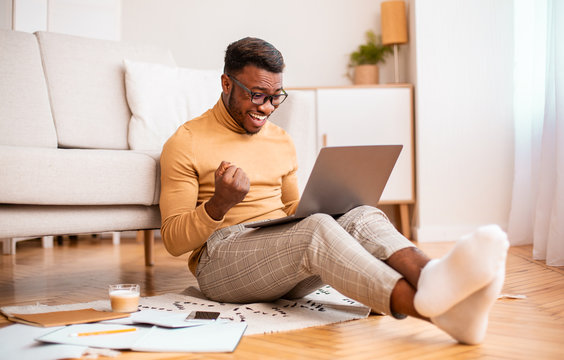 Excited Black Guy Using Laptop Shaking Fists Sitting At Home