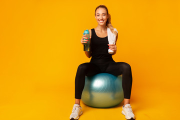 Girl Sitting On Fitball Holding Water Smiling At Camera, Studio