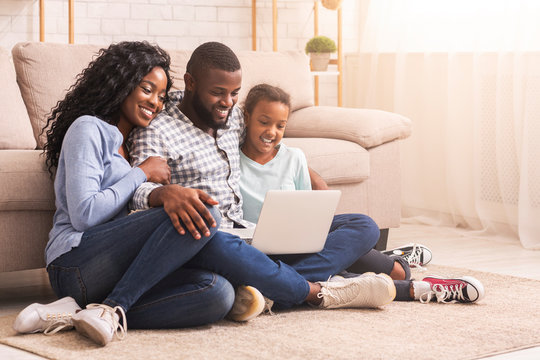 Father, mother and daughter using laptop at home together