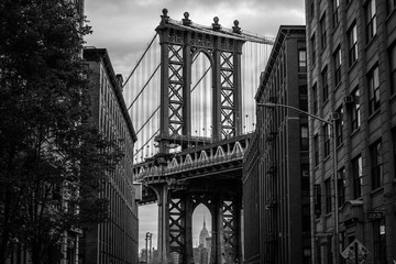View of one of the towers of the Manhattan Bridge from the streets of the DUMBO district, Brooklyn, NYC black and white