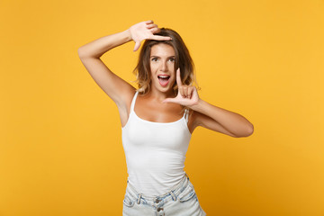 Funny young woman in light casual clothes posing isolated on yellow orange background, studio portrait. People sincere emotions lifestyle concept. Mock up copy space. Making hands photo frame gesture.