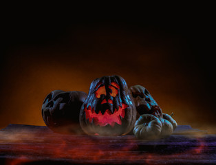 Scary Halloween pumpkins on wood in a spooky place at night. Poster concept.