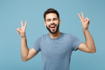 Young laughing funny handsome man in casual clothes posing isolated on blue wall background, studio portrait. People sincere emotions lifestyle concept. Mock up copy space. Showing victory sign.
