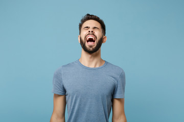 Young frustrated crazy man in casual clothes posing isolated on blue wall background, studio portrait. People sincere emotions lifestyle concept. Mock up copy space. Keeping eyes closed, screaming.