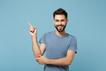 Young handsome smiling cheerful man in casual clothes posing isolated on blue background, studio portrait. People sincere emotions lifestyle concept. Mock up copy space. Pointing index finger aside.