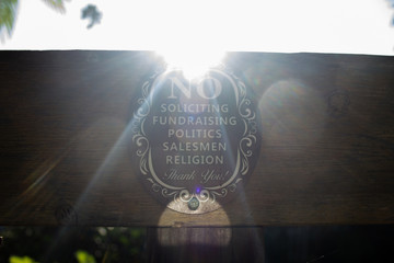 ornate no soliciting sign on wooden fence with sun blast