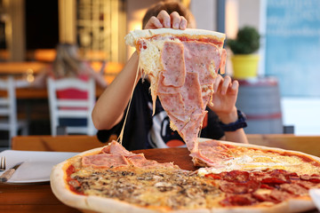 Kid taking big piece of pizza. Enjoying family meal concept