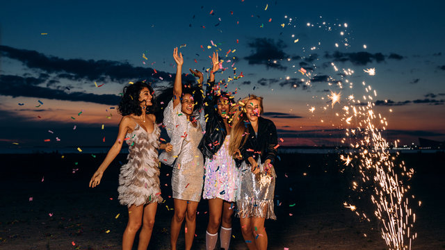 Group of four girlfriends dancing under confetti at sunset. Happy women celebrating with fireworks outdoors at evening.