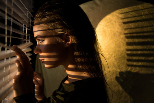 poster style Portrait of young woman looking through  sun blinds window shutter artistic version