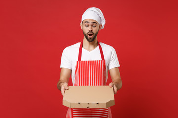 Shocked young bearded male chef cook or baker man in striped apron toque chefs hat posing isolated on red background. Cooking food concept. Mock up copy space. Hold italian pizza in cardboard flatbox.