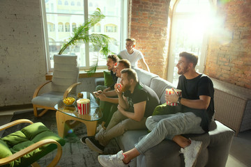 Group of excited friends playing video games at home. Caucasian male gamers or fans spending time and having fun together at home. Emotional watching gameplay. Modern technologies, friendship, weekend