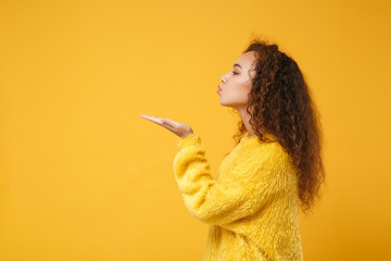 Side view of young african american girl in fur sweater posing isolated on yellow orange background in studio. People sincere emotions lifestyle concept. Mock up copy space. Blowing sending air kiss.
