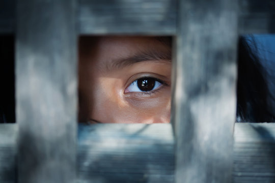 The blank stare of a child's eye who is standing behind what appears to be a wooden cage to convey captivity, or bondwoman.