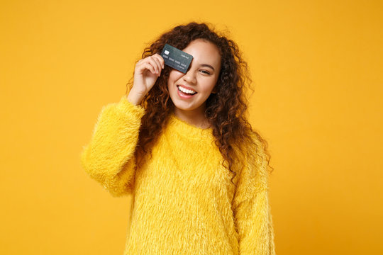 Cheerful young african american girl in fur sweater posing isolated on yellow orange wall background studio portrait. People lifestyle concept. Mock up copy space. Covering eyes with credit bank card.