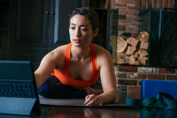 Direct view of a woman exercising while referring to laptop