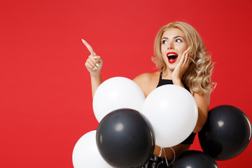 Excited young woman girl in black clothes posing isolated on red background. Women's Day birthday holiday party concept. Mock up copy space. Celebrating hold air balloons, pointing index finger aside.