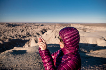 Woman taking photograph of rocky landscape