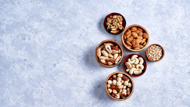 pecans, hazelnuts, almonds, pine nuts, Brazil nut, cashews in wooden bowls on blue background, top view, flat lay